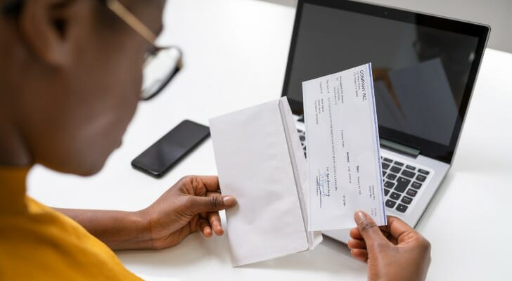 Image shows a woman who is wearing glasses sitting at a desk in front of a laptop and removing a paycheck from an envelope in her hands. SmartAsset analyzed data to find the best cities for women's pay.