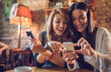 Two smiling women look at credit monitoring apps on their cellphones.