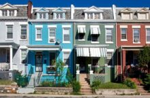 A row of colorful townhouses on a sunny day.