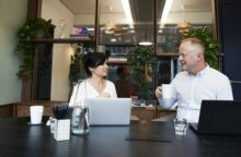 A man and woman chat in an office
