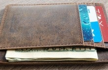 A closeup of a brown wallet with various cards and dollar bills